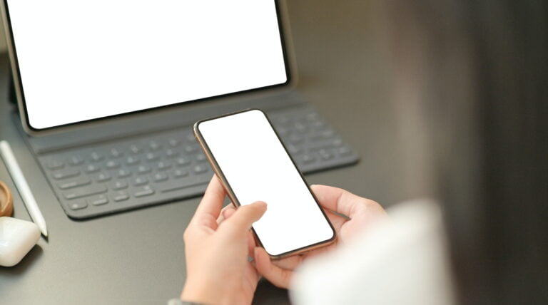 Close up image of the hand of a businesswoman is using a blank screen smartphone with a laptop.