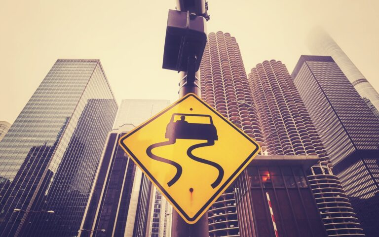 Color toned slippery road sign with Chicago skyscrapers.