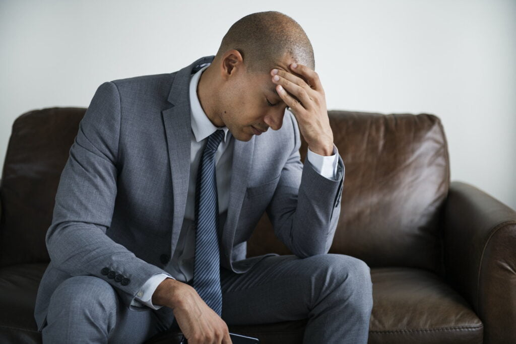 Depressed busines man sitting on a couch