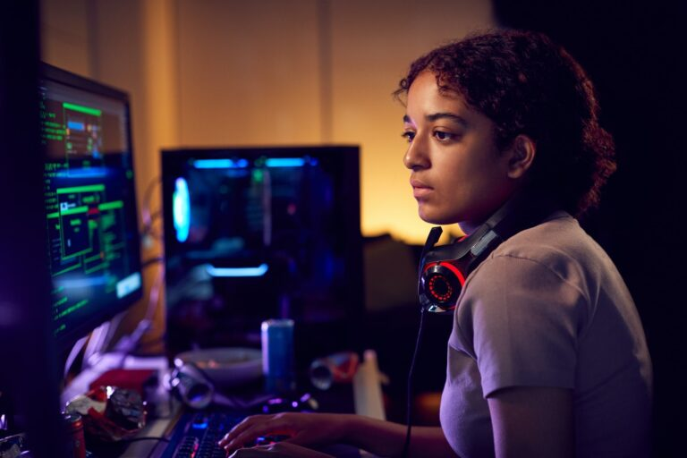 Female Teenage Hacker Sitting In Front Of Computer Screens Bypassing Cyber Security