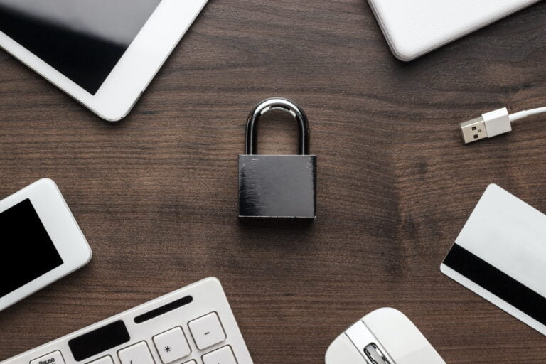 padlock and different gadgets on the wooden office table