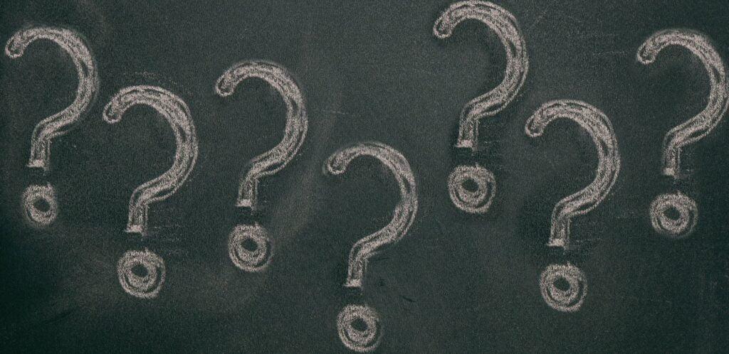 Question marks chalk drawing on blackboard background