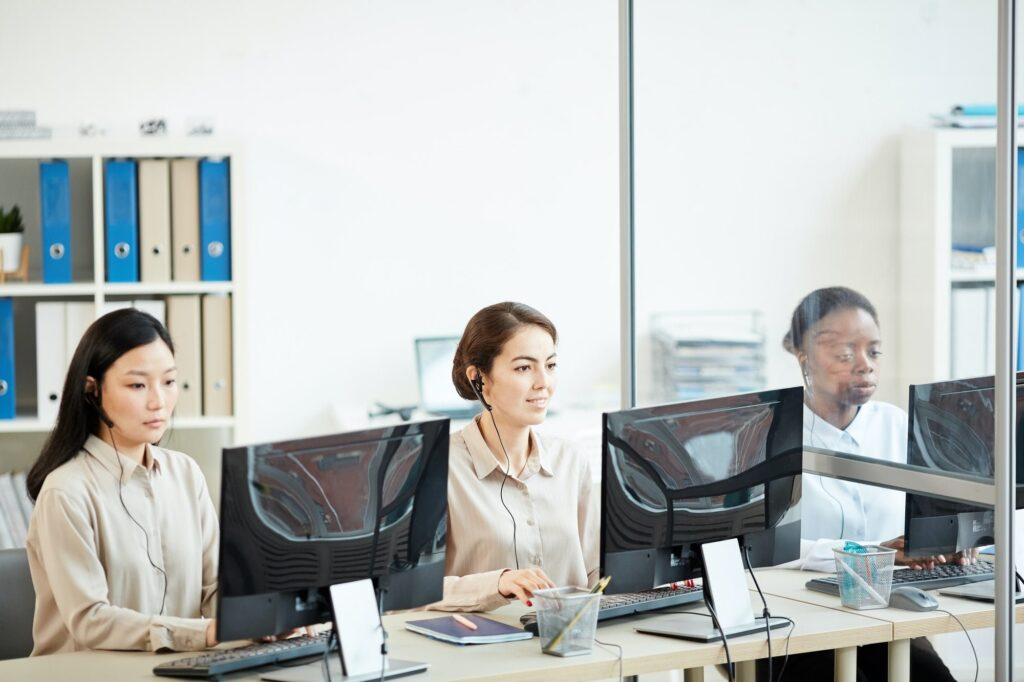 Row of Female Operators in Call Center working to improve customer experience