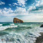 Sea waves crashing on the shore and flowing above seashore pebbl