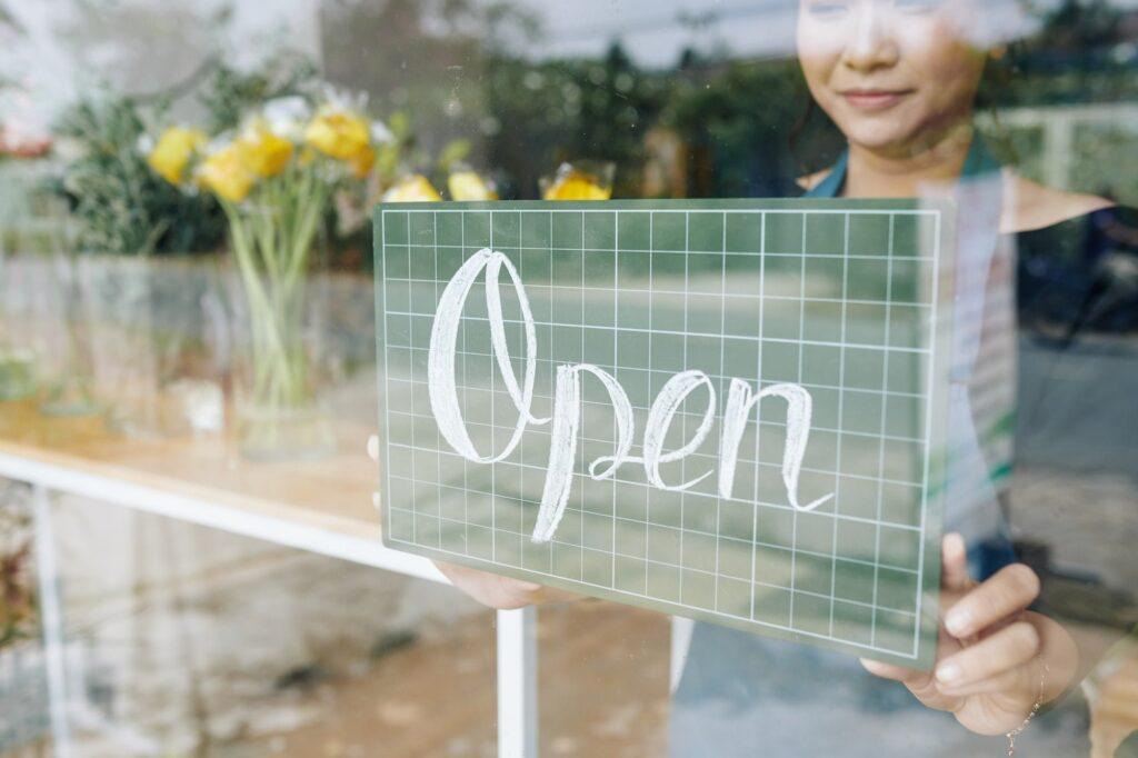 Shop owner hanging open sign