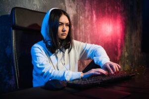 Woman hacker wearing an hood in front of computer screen