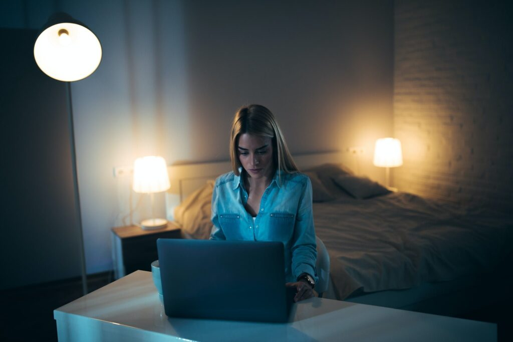 Woman teleworking from her bedroom late at night.