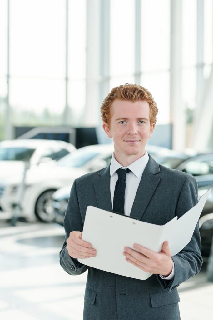 Young manager of contemporary car center holding open folder with documents