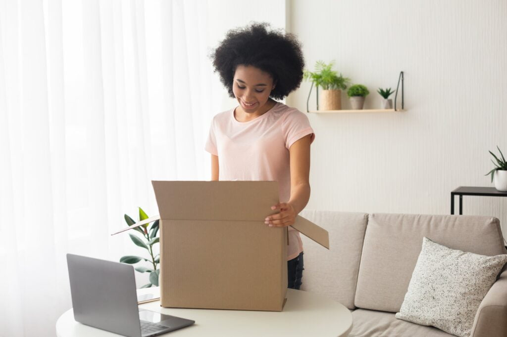 Smiling african american woman, near box and laptop. Posted in how to move your computer without damaging it.