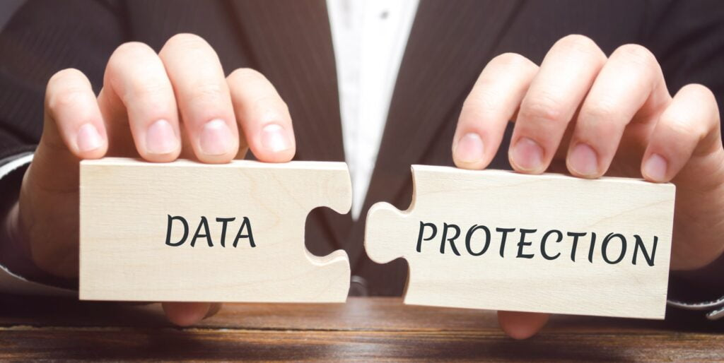 Businessman collects wooden puzzles with the word Data Protection