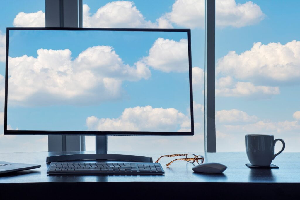 Conceptual cloud computing desk with computer, keyboard, mouse, eyeglasses and coffee.